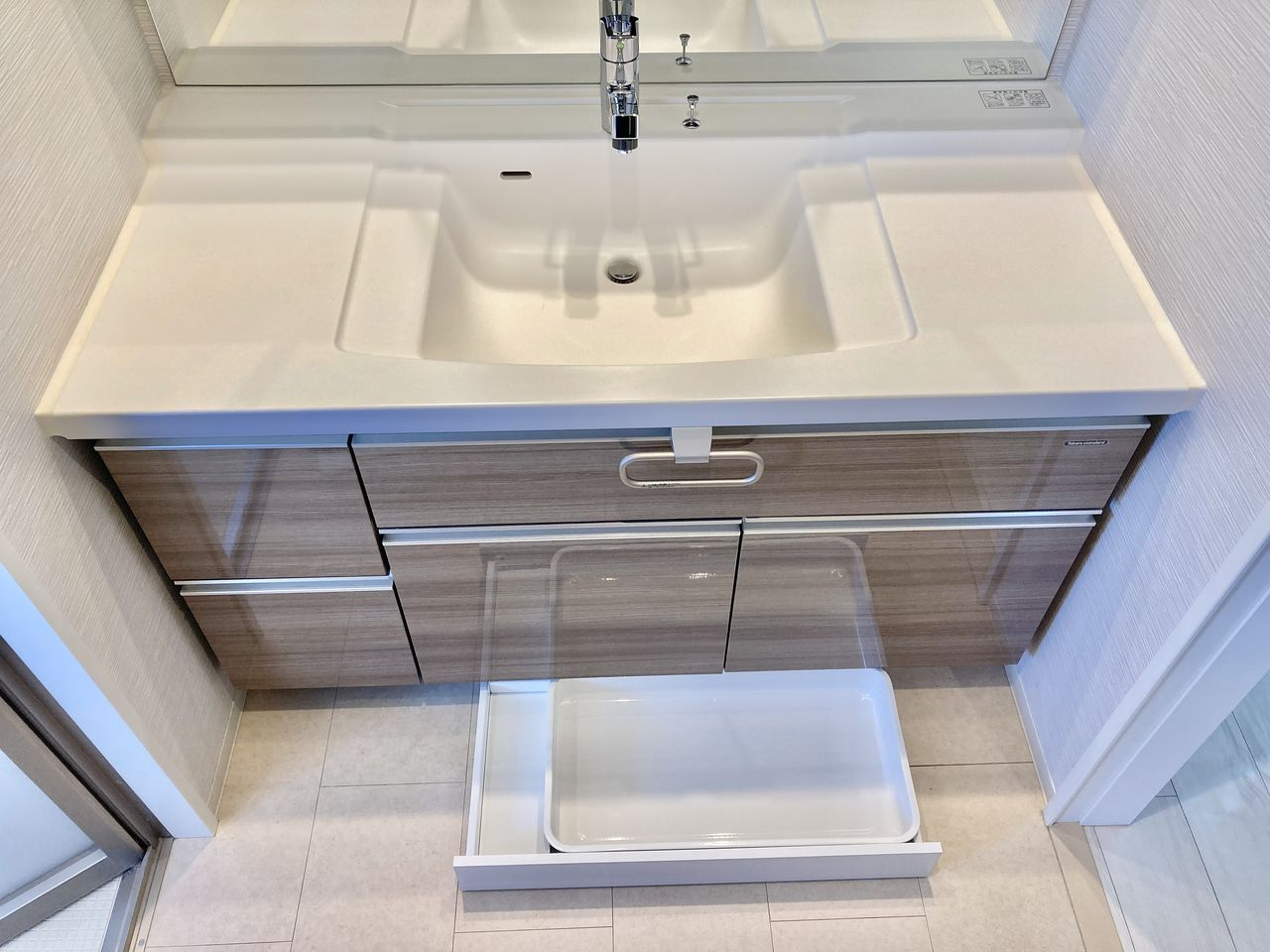 栓化粧台と床の間に洗面所内をスッキリ片付けるヘルスメーター収納スペースや足元収納が設けられています。