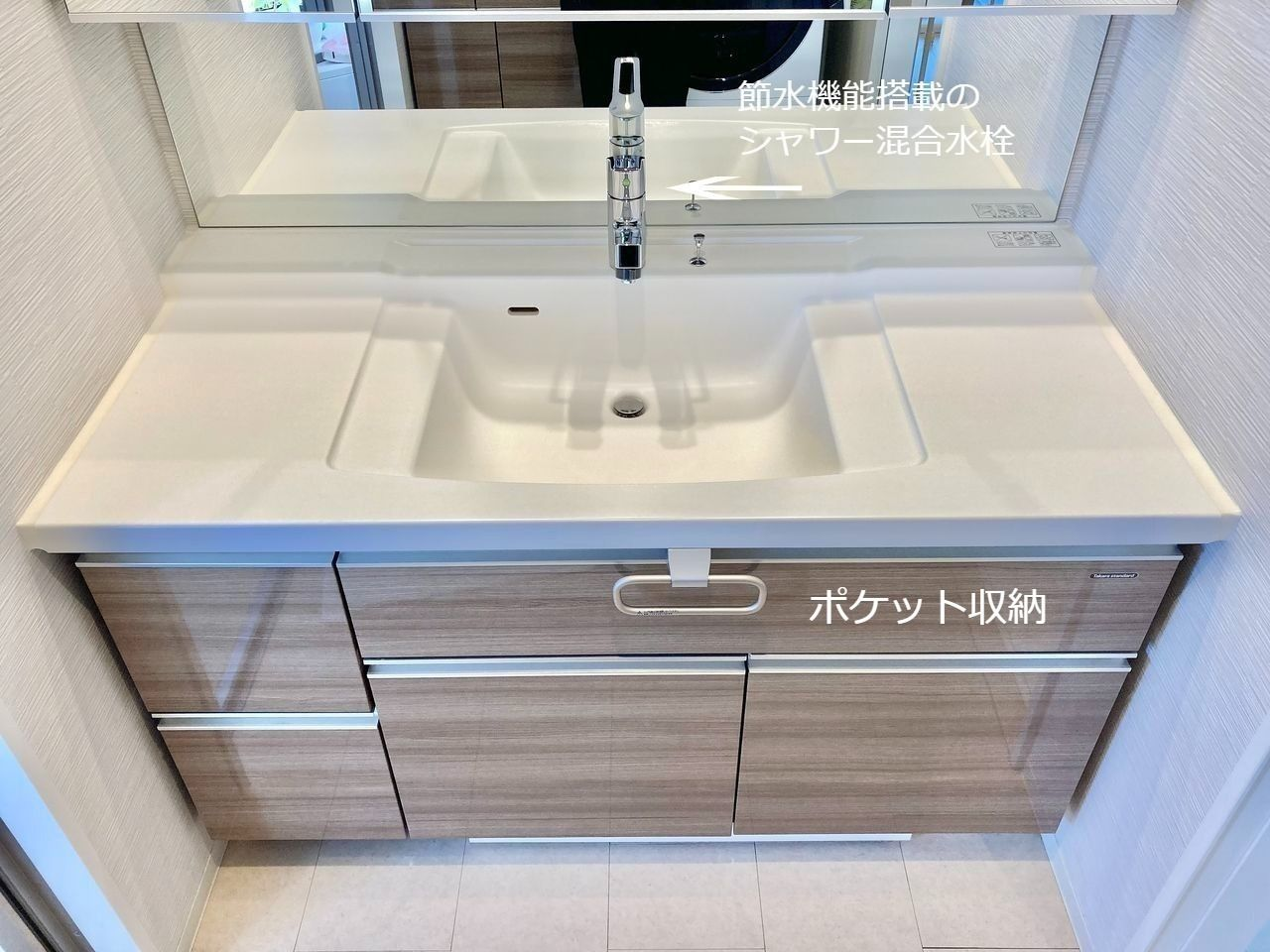 人造大理石の洗面カウンターには便利な段差を設けました。濡れたものと乾いたものを置き分けられます。洗面器はつなぎ目のない一体成形なので、汚れにくく、お掃除もかんたんです。