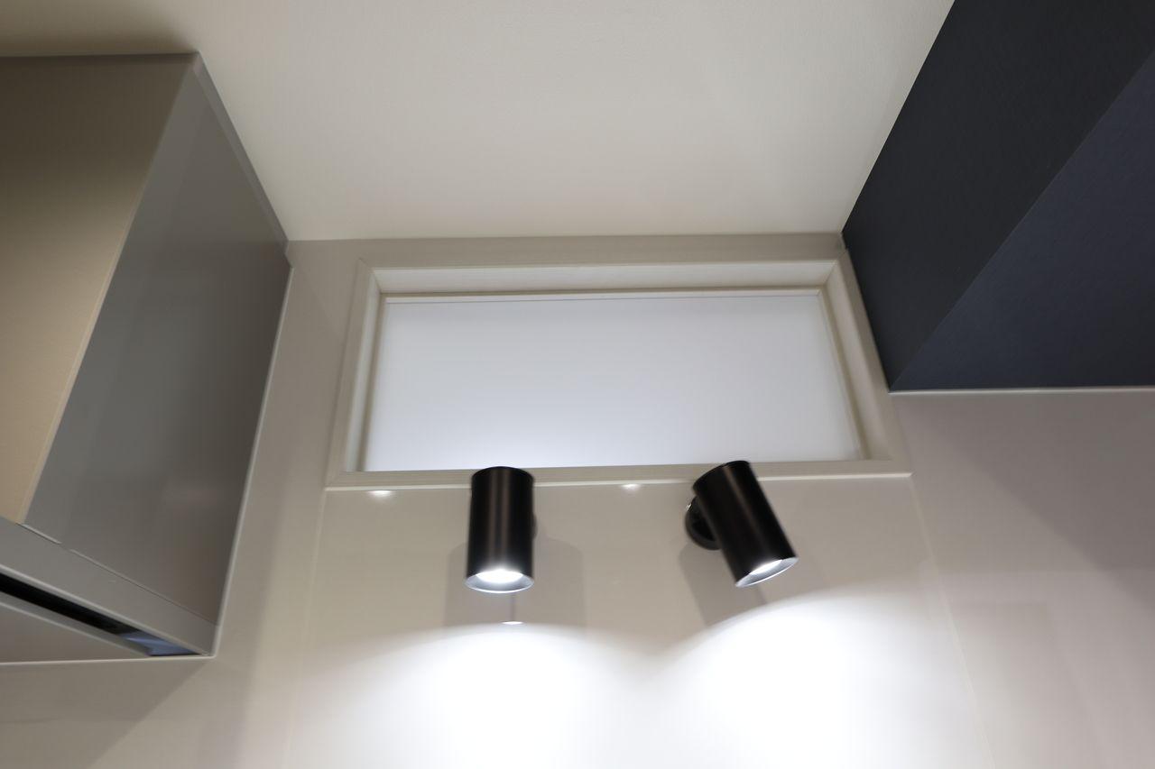 キッチンシンクの高い位置に明り取り窓を設けて、さらにスポットライトで手元に照明があたるようになっています。