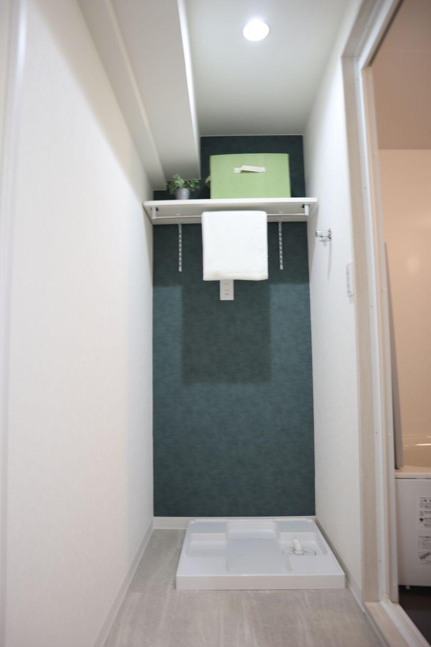 洗面室の洗濯置場の背面の壁はアクセントクロス。深緑系のアクセントクロスが、落ち着いた印象に!